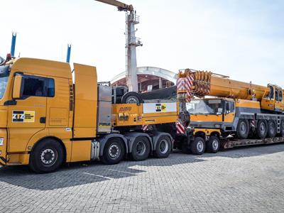 Beautiful optical combination of a yellow semi-trailer truck, a mobile crane and a low loader.  The Eurocompact model from Scheuerle or the THP model from Goldhofer have similar characteristics to the CombiMAX modular vehicle.